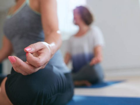 Woman sitting with her legs crossed and hand resting on knee. Close up of meditating woman's hand during yoga class. Lotus pose meditation.